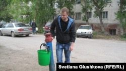 Алексей Палий набирает воду у колонки. Астана, май 2013 года.