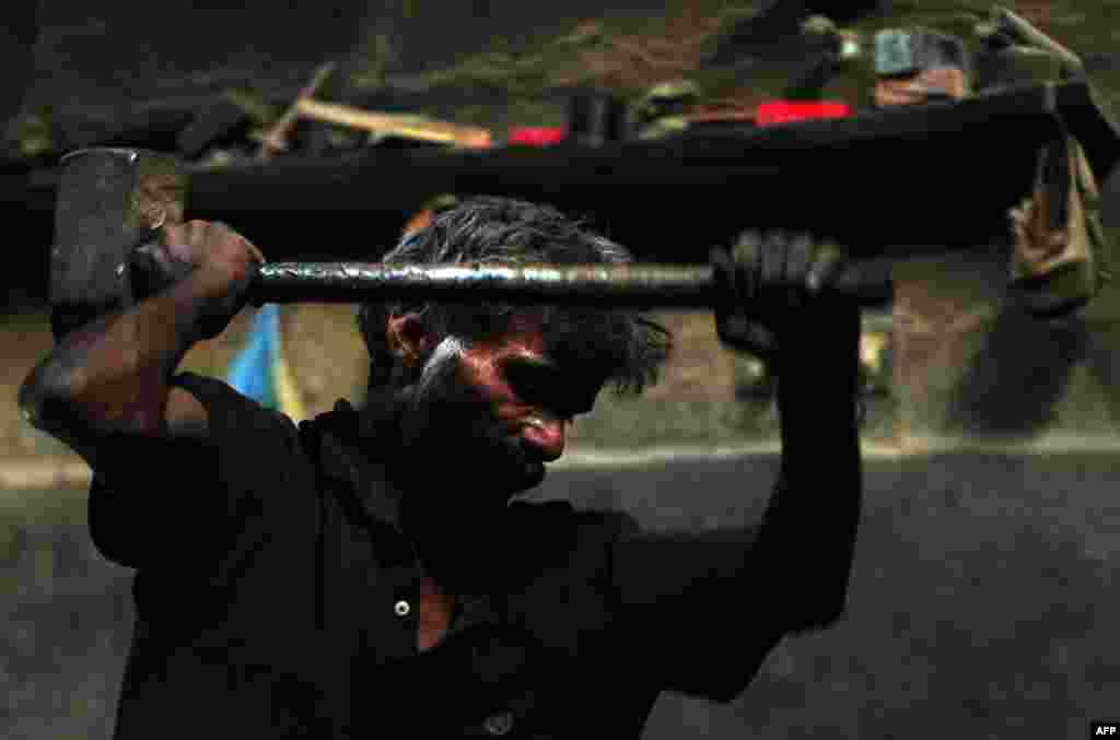 A Pakistani laborer uses a sledgehammer as he works at an iron factory in Karachi. (AFP/Asif Hassan)