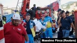 Медики и спасатели на месте обрушения автомобильного моста в Генуе.