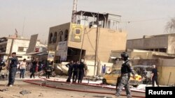 Iraqi security personnel stand at one of the sites of a bomb attack in Baghdad on April 15.