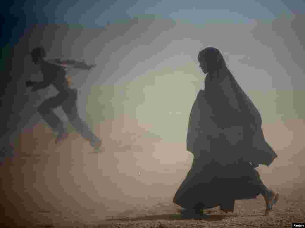 Somali refugees run from the dust at Ifo camp near Dadaab, about 80km (50 miles) from Liboi on the border with Somalia in north-eastern Kenya, January 8, 2007. Aid agencies are operating three large refugee camps in Dadaab where about 160,000 Somali refugees are held and said they could provide more staff to help Kenya with any new influx. REUTERS/Radu Sigheti