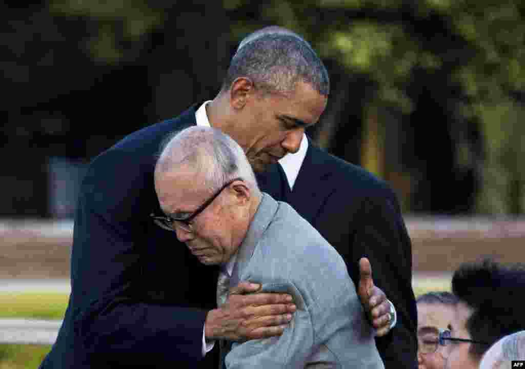 აშშ-ის პრეზიდენტი ბარაკ ობამა ეხვევა 1945 წელს ჰიროსიმაში ატომურ დაბომბვას გადარჩენილ შიგეაკი მორის. ობამა აშშ-ის პირველი მოქმედი პრეზიდენტია, ესტუმრა ჰიროსიმის მშვიდობის მემორიალურ პარკს. (ფოტო: AFP)