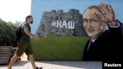 Сімферополь, чоловік проходить повз стіну з зображенням графіті президента Росії Володимира Путіна, 17 серпня 2015 (ілюстраційне фото)