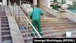 Работник коммунальной службы моет ступени, ведущие к входу в здание министерства труда и социальной защиты населения. Нур-Султан, 10 июня 2020 года.