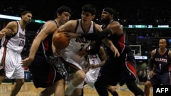 Zaza Pachulia (second from left) and Josh Smith of the Atlanta Hawks surround Ersan Ilyasova (center) of the Milwaukee Bucks as they battle for the ball during a 2010 NBA playoff game in Milwaukee.