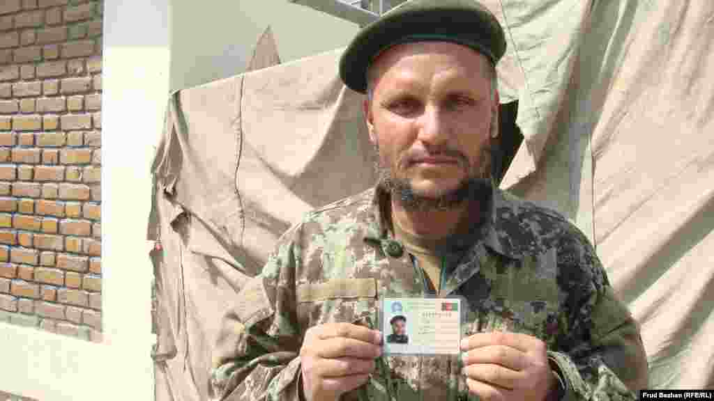 An Afghan soldier gets a new voter card.