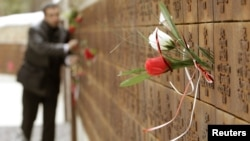 A man puts flowers into a wall with the names of slain Polish officers during a commemoration ceremony at a memorial complex in Katyn on April 10.