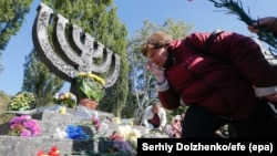A Ukrainian woman lays flowers at the monument to victims during a mourning ceremony near the Babi Yar site in Kyiv on September 29.