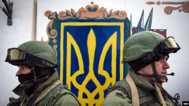 Так называемые «зеленые человечки» стоят на КПП возле въезда в украинскую военную часть в Перевальном возле Симферополя во время операции по захвату Крыма российскими войсками, 2 марта 2014 года