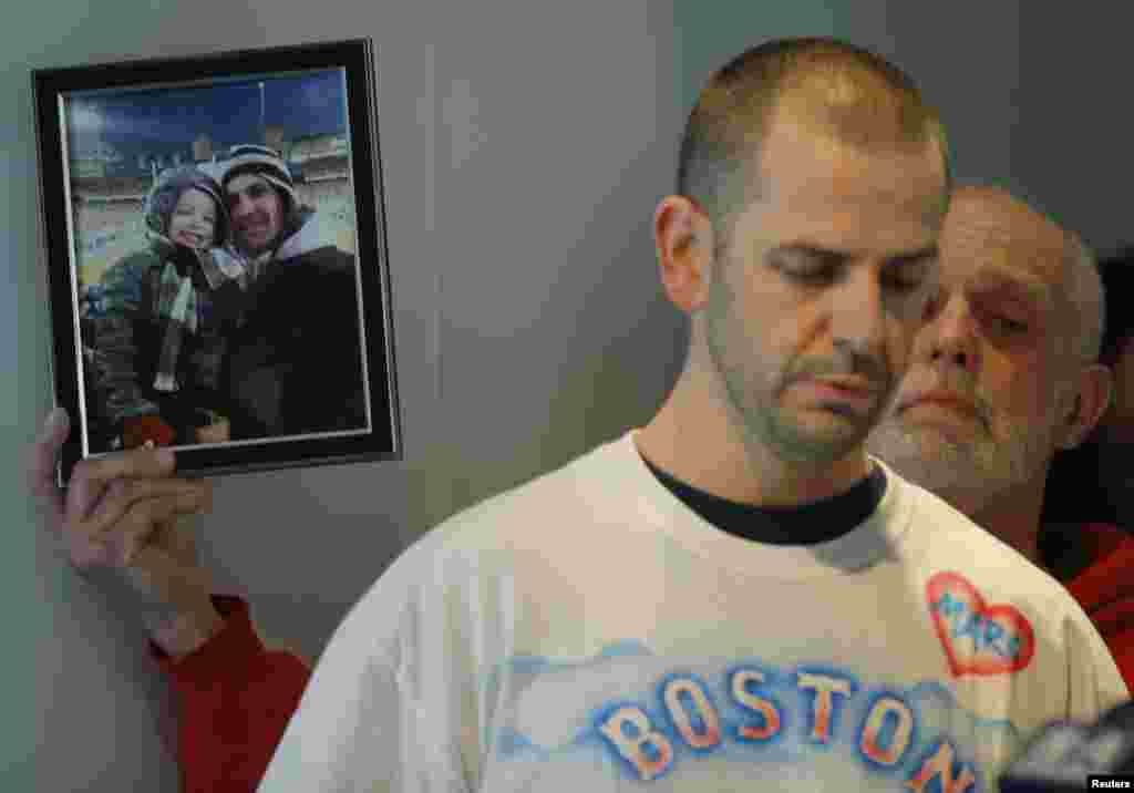 Edward Fucarile, the father of Boston Marathon bombing victim Marc Fucarile, holds up a photograph of his son as his family read a statement about his condition at Massachusetts General Hospital in Boston. Marc Fucarile's injuries included having his right leg amputated, multiple fractures in his left leg, and shrapnel in his body, including his heart.