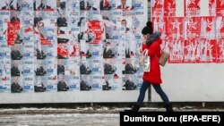 A girl talks on her mobile phone while passing a panel with campaign posters in downtown Chisinau, Moldova (February 13, 2019)