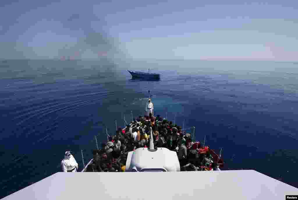 A group of 300 sub-Saharan Africans sit on board the Italian Finance Police vessel Di Bartolo as their boat is left to drift off the coast of Sicily. (Reuters/Alessandro Bianchi)