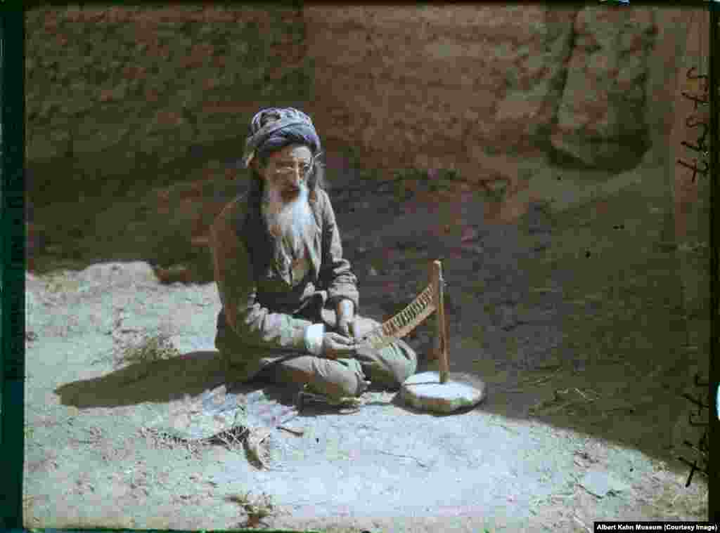 A goldsmith at work in a mud-walled courtyard in Kabul. These 1928 images, made by photographer Frederic Gadmer, form part of the Archives of the Planet project, which aimed to capture the world with large-format color photographs.