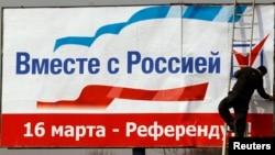 Қырым халқын референдумға шақырған билборд іліп жатқан адам. Симферополь, 12 наурыз 2014 жыл.