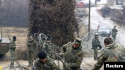 Kosovo -- KFOR soldiers from Germany remove a barbed wire from the road in the village of Jagnjenica, 06Dec2011