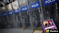 Сотрудники турецкой полиции стоят напротив участников акции протеста. Стамбул, 5 января 2014 года.
