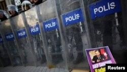 Полицейские стоят напротив участников акции протеста, требующих отставки правительства Эрдогана. Стамбул, 5 января 2014 года.