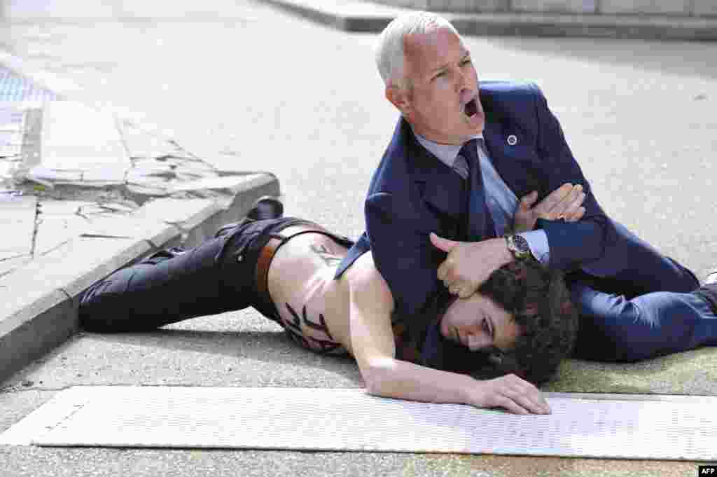 """A security guard pins a Femen activist to the ground after she and other activists tried to stop the car of Tunisian Prime Minister Ali Larayedh from leaving the EU commission building in Brussels. They shouted """"Free Amina!"""" -- a reference to Amina Sboui, a teenage anti-Islamist feminist who is being held in a Tunisian jail. (AFP/Georges Gobet)"""