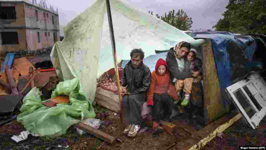 A Roma family of Turkish origin sits under an improvised shelter to protect from heavy rain in the coastal Romanian town of Eforie Sud on September 30. Romanian authorities evicted around 100 Roma from the town, near the Black Sea coast, without providing them with alternative housing. (AFP/Mugur Varzariu)