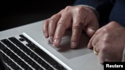 U.S. -- A cyber warfare expert works on his Apple laptop computer during a portrait session in Charlotte, North Carolina, 01Dec2011