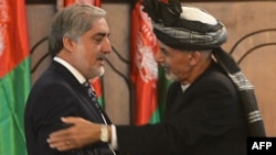 Newly-sworn in Afghan President Ashraf Ghani (R) embraces to Abdullah Abdullah, Afghan new Chief Executive, during the swearing in ceremony for the country's new president at the Presidential Palace in Kabul, September 29, 2014.