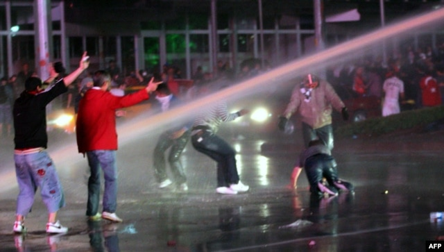 Protesters take cover from water cannons during clashes with police in Ankara on June 8.