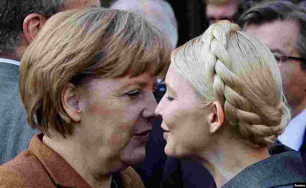German Chancellor Angela Merkel (left) is greeted by Ukrainian opposition leader Yulia Tymoshenko after a meeting of the European People's Party in Meise, Belgium, in March 2011.