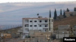 "An Islamic State flag is seen atop a building in Kobani. The Kurds have suggested that Kobani has become an ""obsession"" for Islamic State."