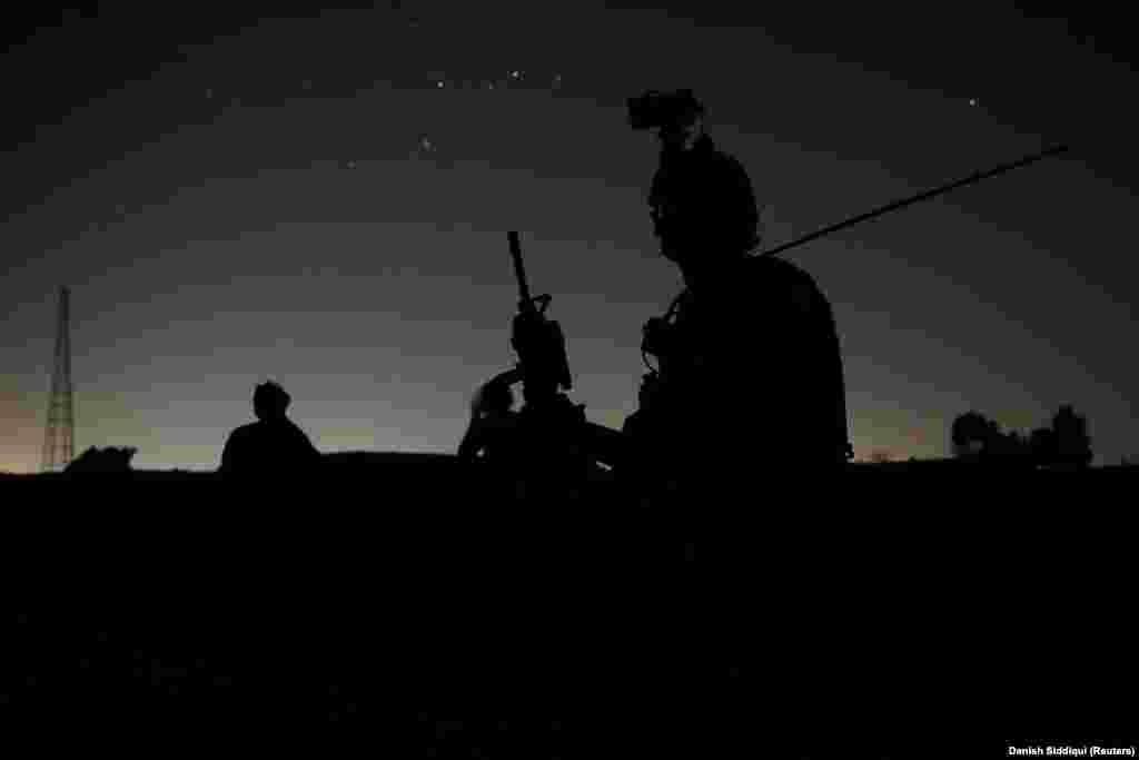 Члены афганских спецназовцев следят за обысками домов в деревне во время боевой операции против талибов в провинции Кандагар