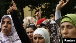 Muslim women protest against the government's decision to ban pupils from wearing head scarves in public schools.
