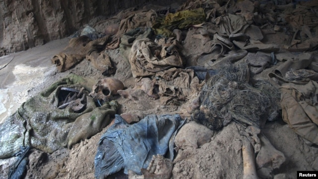 Human skeletons and items of clothing are seen in a mass grave uncovered in northern Balkh Province in January. Construction workers digging a car park found at least 10 human skulls.