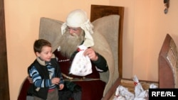 Товлис Бабуа (так в Грузии называют Деда Мороза) раздает подарки
