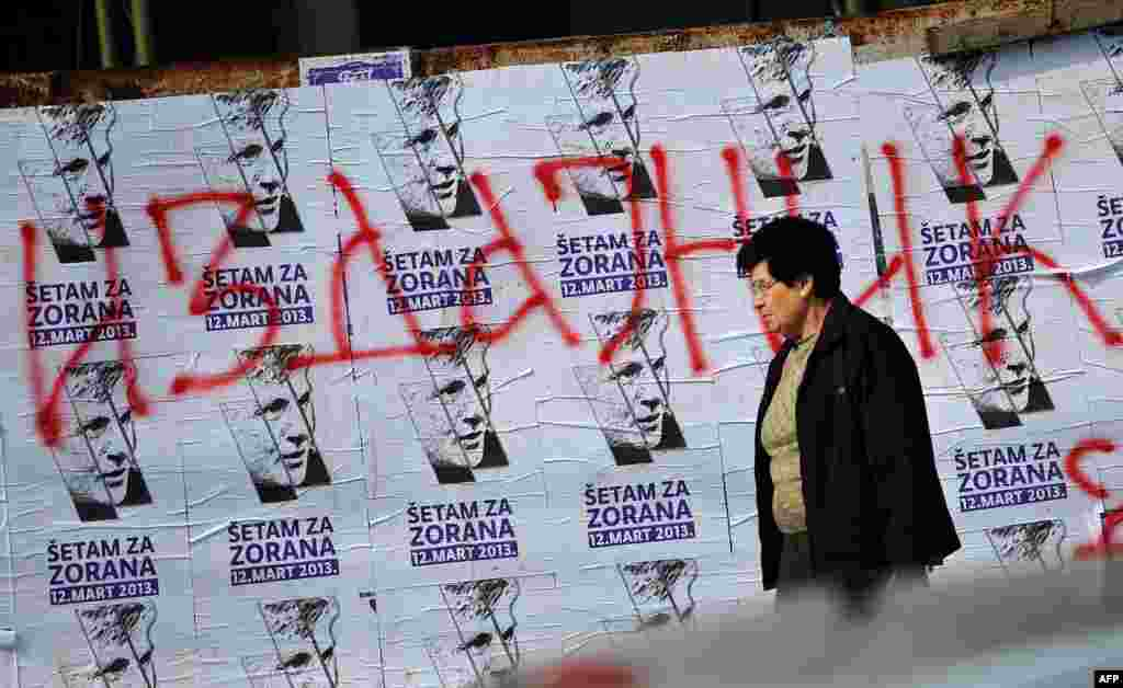 A woman walks past placards announcing the commemorative march in the Serbian capital to mark the 10th anniversary of Djindjic's assassination. (AFP/Andrej Isakovic)