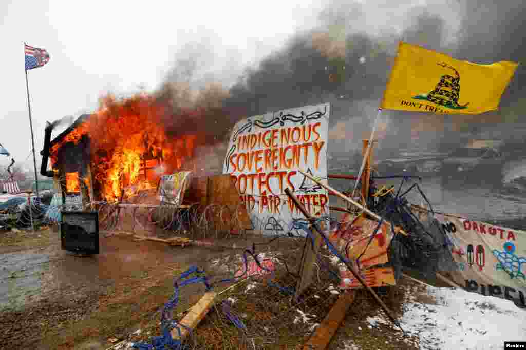 A structure burns after being set alight by protesters preparing to evacuate the main opposition camp against the Dakota Access oil pipeline near Cannon Ball, North Dakota. (Reuters/Terray Sylvester)