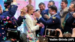 Ukraine's president-elect Volodymyr Zelenskiy and his wife, Olena Zelenska, greet their supporters at his headquarters after his election victory on April 21.