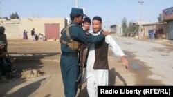 Сотрудник афганских сил безопасности проверяет прибывающих для голосования избирателей. Провинция Гильменд, 6 апреля 2014 года.