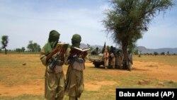 Në këtë fotografi shihen dy luftëtarë të rinj duke lexuar vargje kuranore, me kërkesë të komandantëve të tyre islamikë në Douentza, Mali. Fotografi nga arkivi.