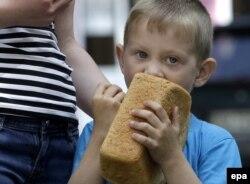 Мальчик ест хлеб, выданный как гуманитарная помощь, Донецк, 3 июня 2015 года