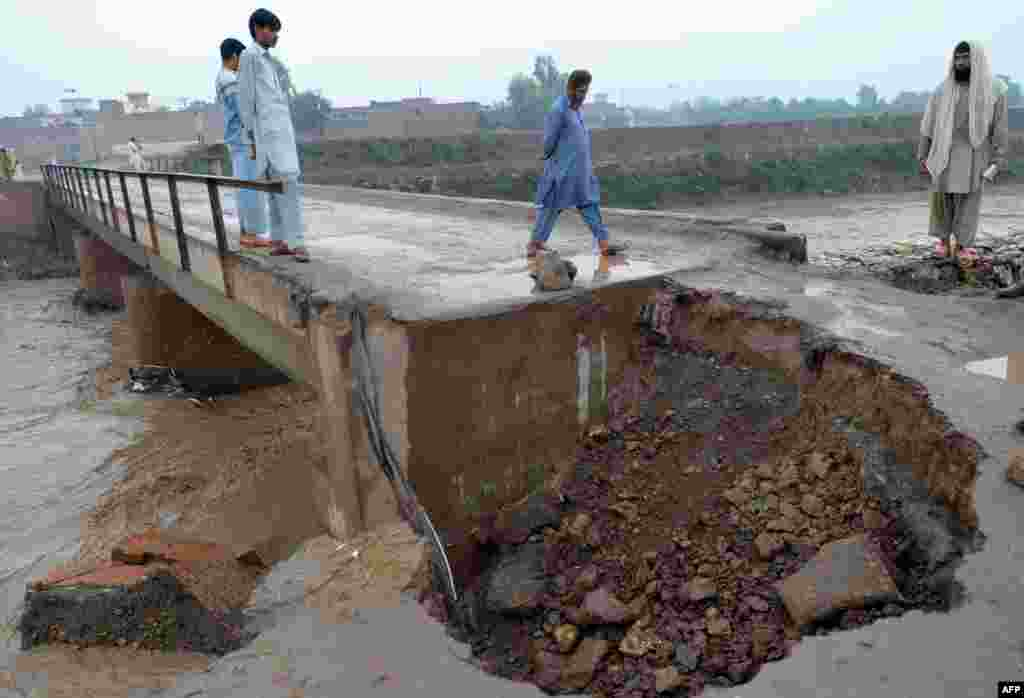 Pakistanis walk on a damaged bridge over a flooded river in Peshawar.