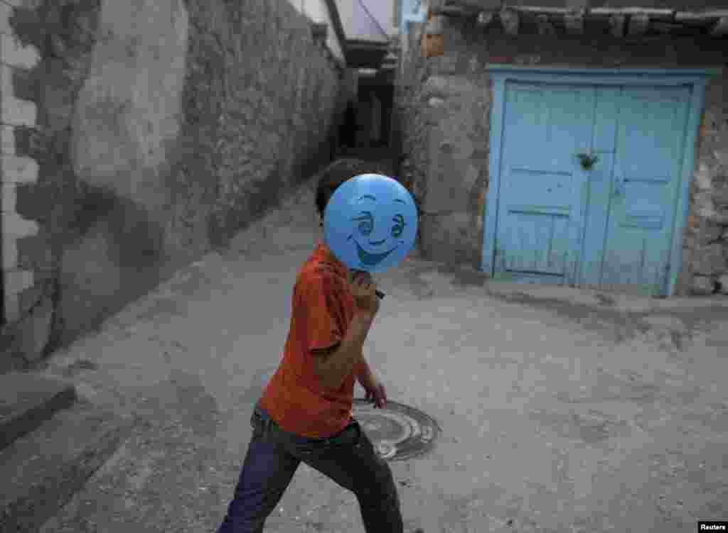 A boy hides his face behind a balloon on a street in Gimry.