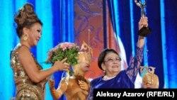 Хозяйка фестиваля «Алма-Ата — моя первая любовь» Дарига Назарбаева вручает фестивальную статуэтку певице Бибигуль Тулегеновой. Алматы, 6 сентября 2014 года.