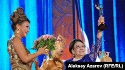 Дарига Назарбаева вручает награду певице Бибигуль Тулегеновой