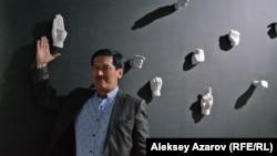 Суретші Арыстанбек Шалбаев инсталляциясының қасында тұр. Алматы, 8 мамыр 2019 жыл.