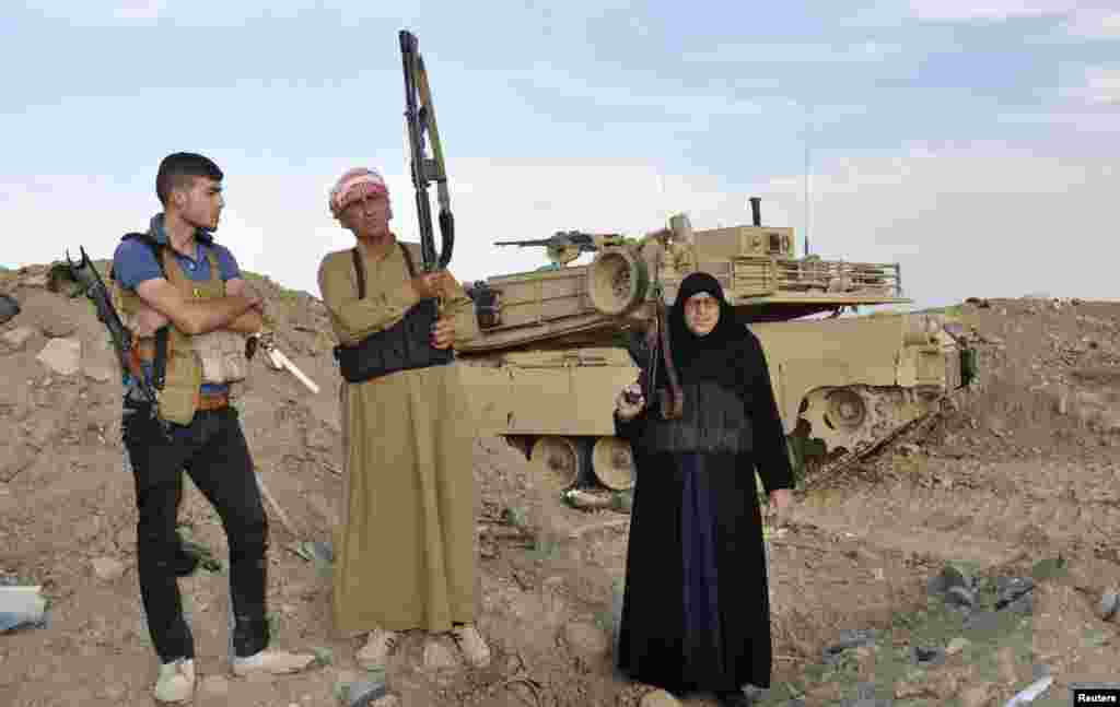 Un Muayad (right) a Ramadi resident fighting alongside tribal fighters, poses with her fellow fighters during clashes with the Al-Qaeda-linked Islamic State of Iraq and the Levant in Ramadi  on May 19. (Reuters)
