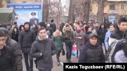 Молодые люди идут на фоне растяжки с изображением президента Казахстана и надписью: «Долг, честь, отвага».