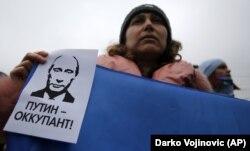 Женщина держит плакат с надписью «Путин - оккупант» во время митинга против российской аннексии Крыма. Симферополь, 11 марта 2014 года
