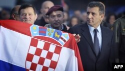 Mladen Markac (left) holds a national flag next to Ante Gotovina (right) upon their arrival at Zagreb airport on November 16.