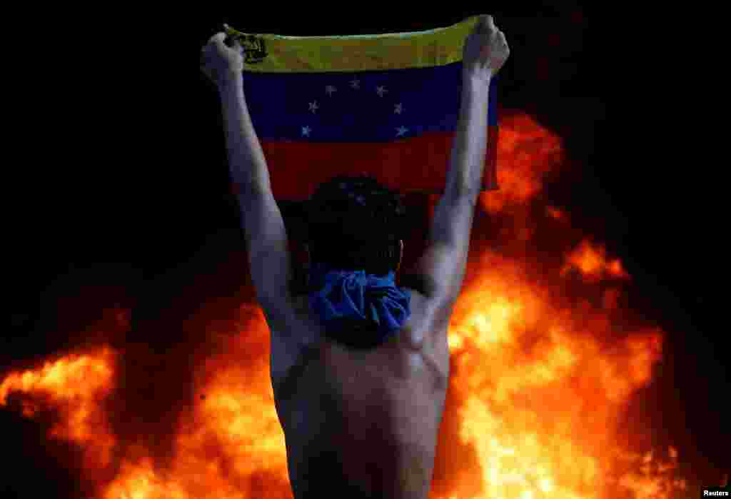 A protester holds a national flag as a bank burns during a rally against Venezuela's President Nicolas Maduro, in Caracas, Venezuela, June 12, 2017. (Reuters/Carlos Garcia Rawlins)