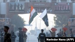 Pakistani Rangers (in black) and Indian Border Security Force personnel take part in the daily retreat ceremony at the India-Pakistan Wagah Border Post in Kashmir on December 18.