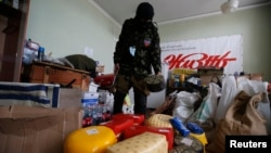 An armed pro-Russian militiaman from the Vostok Batallion looks at items that, according to him, were looted by other separatist groups and stored in the Donetsk regional administration building on May 29.